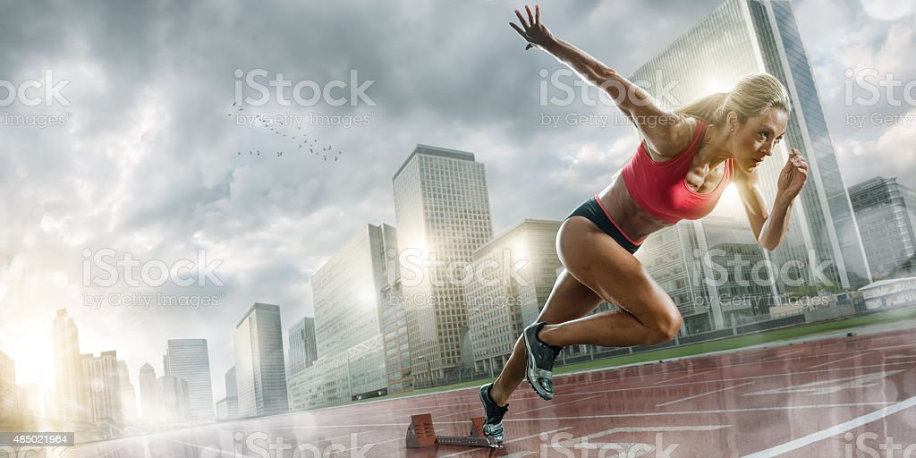Woman Athlete Sprinting in Wet City stock photo