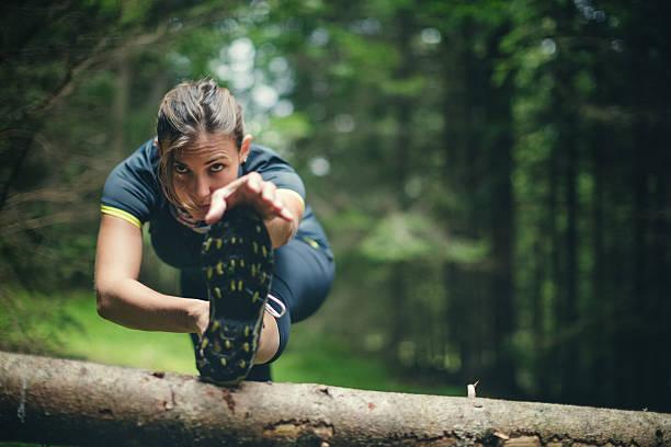 atleta mujer estiramiento en el bosque después de correr - trail running fotografías e imágenes de stock