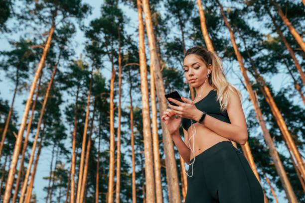 sportlerin sommerwald. in der hand hört smartphone musikkopfhörer. freier raum, online-anwendung im internet, chat in sozialen netzwerken. wählen sie die playlist für die laufende kulisse von bäumen. - wortarten bestimmen übungen stock-fotos und bilder
