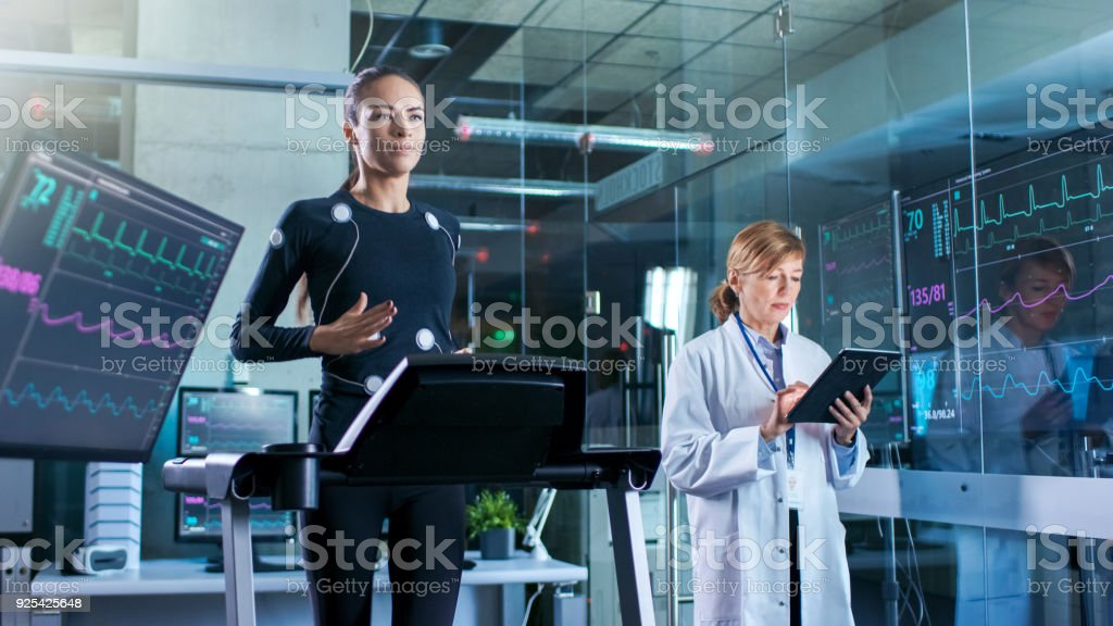 Woman Athlete Walks on a Treadmill  with Electrodes Attached to Her Body while Scientist Holding Tablet Computer Supervises whole Process. In the Background Laboratory with Monitors Showing EKG Readings. stock photo