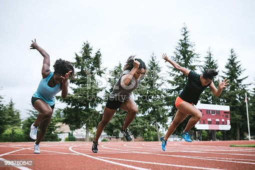A group of young women on the starting line, focused and ready to sprint at full speed.  Training starts for their next track and field competition.