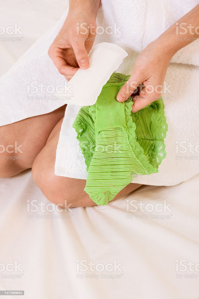 Woman attaching a panty liner to green underwear stock photo