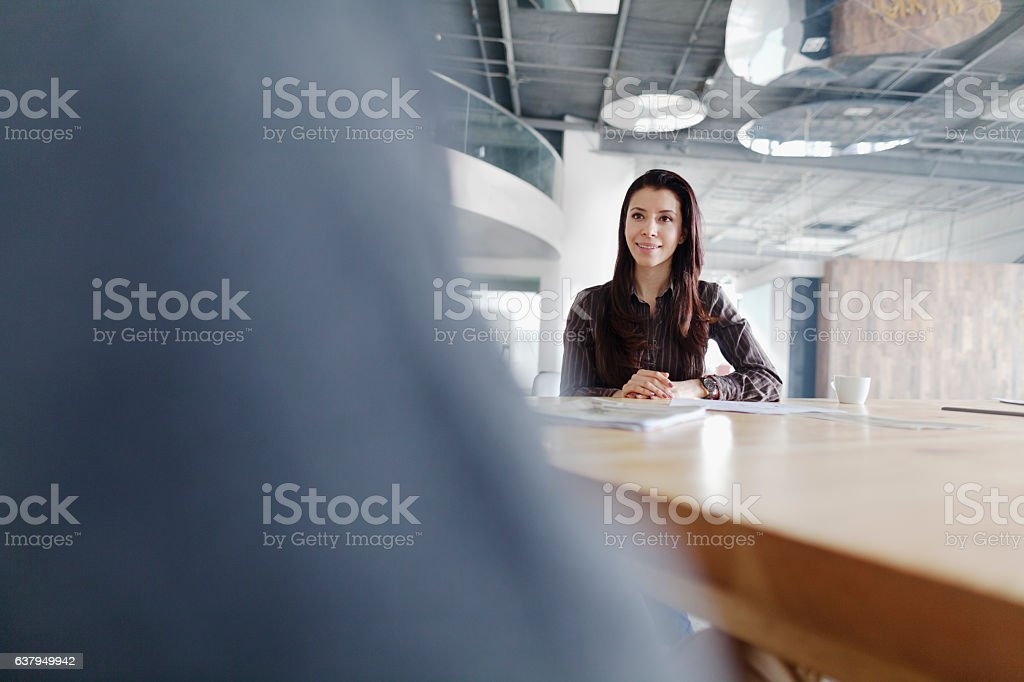 Woman attending business meeting in large studio office stock photo