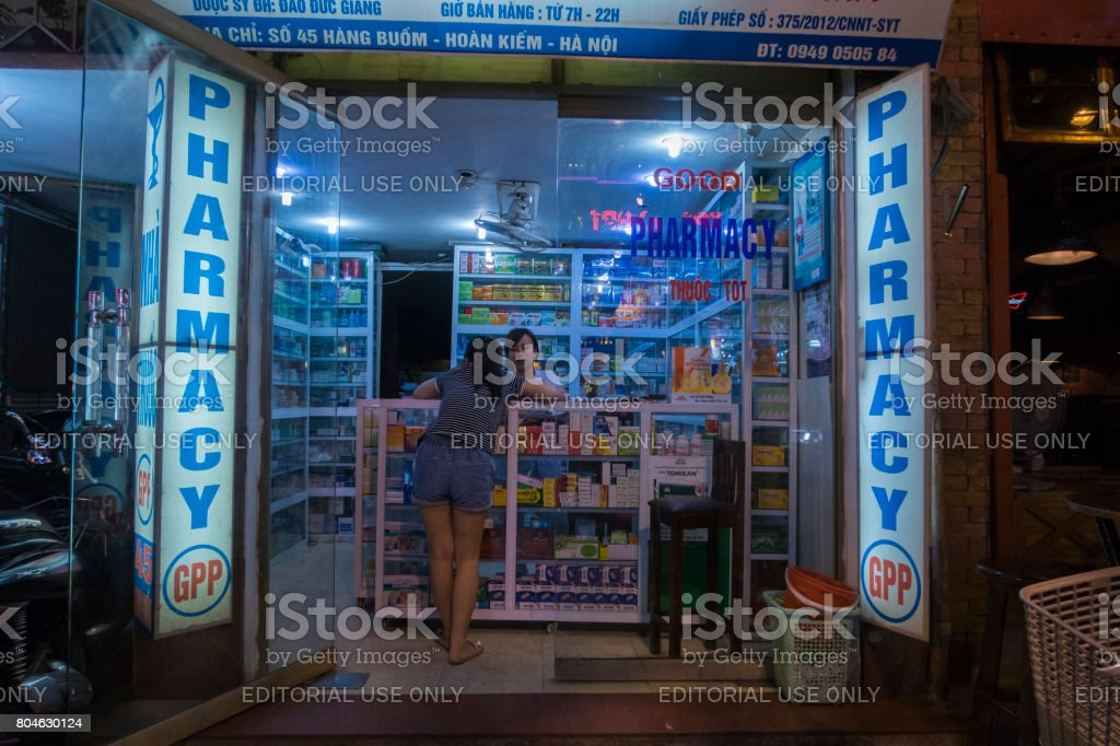 A woman attends a pharmacy in the old quarter of Hanoi stock photo