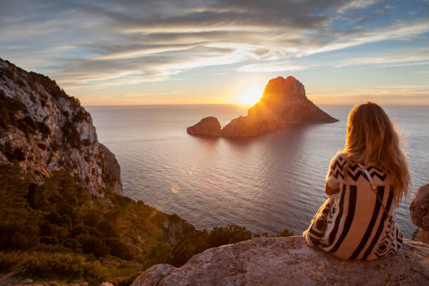 woman back to the front watching a beautiful sunset at the beach. the beach is called es vedra, in ibiza and belongs to balearic islands, in spain - ibiza imagens e fotografias de stock