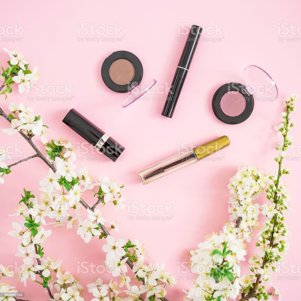 Woman background. White flowers and woman cosmetic - lipstick, mascara on pink background. Flat lay, top view. royalty-free stock photo