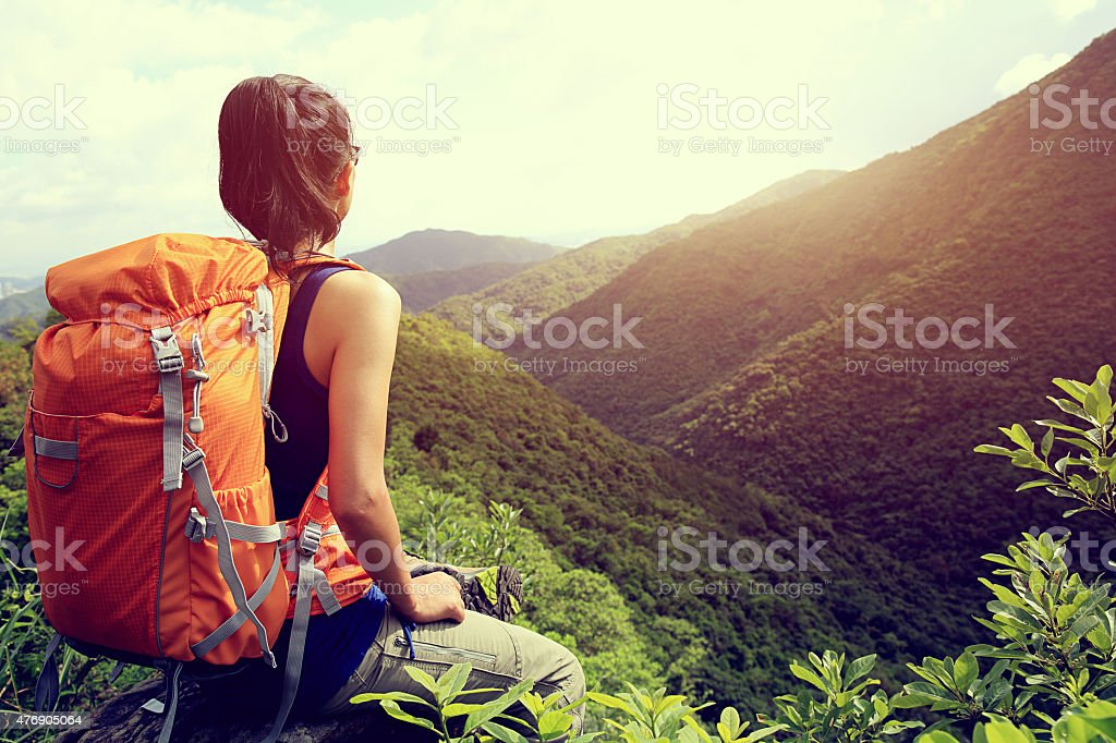 woman backpacker enjoy the view at mountain peak cliff woman backpacker enjoy the view at mountain peak cliff 2015 Stock Photo
