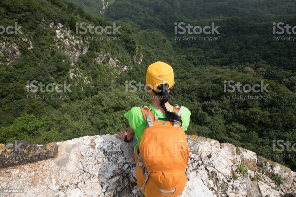 woman backpacker enjoy the view sit on top of mountain royalty-free stock photo