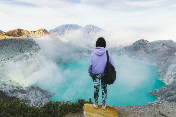 Woman backpacker enjoying the scenic view of turquoise colored lake in the crater of Ijen volcano and mountains on East Java, Indonesia stock photo