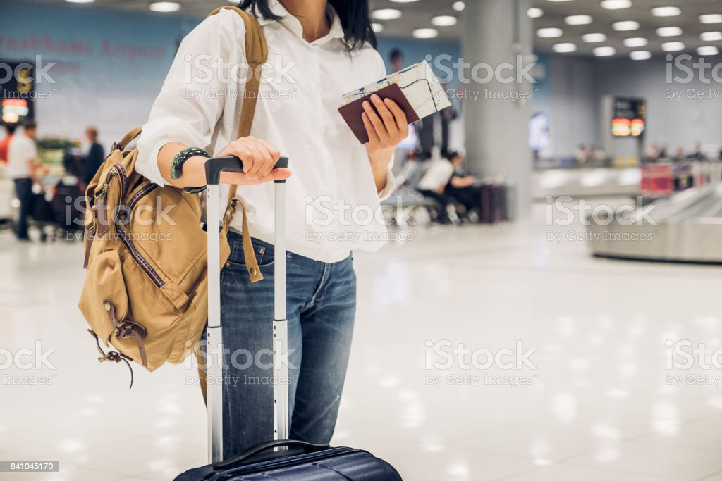 Woman backpacker holding passport and map with suitcase standing at check in baggage at airport terminal,traveler concept stock photo