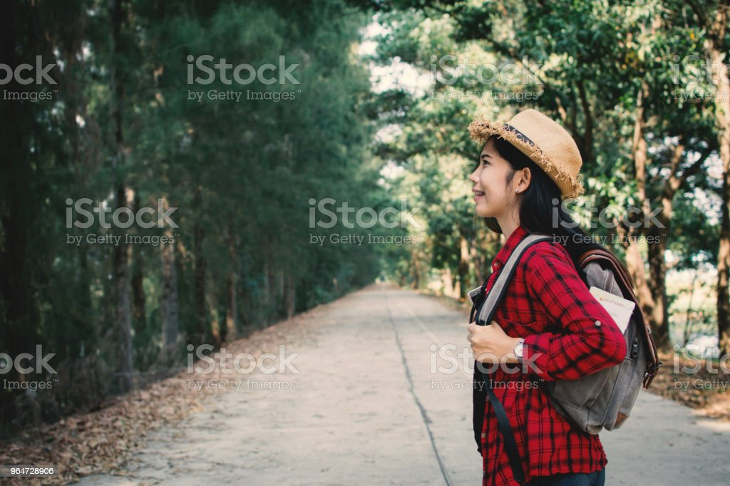 Woman backpacker in the road and forest background, Relax time on holiday concept travel ,color of vintage tone and soft focus royalty-free stock photo