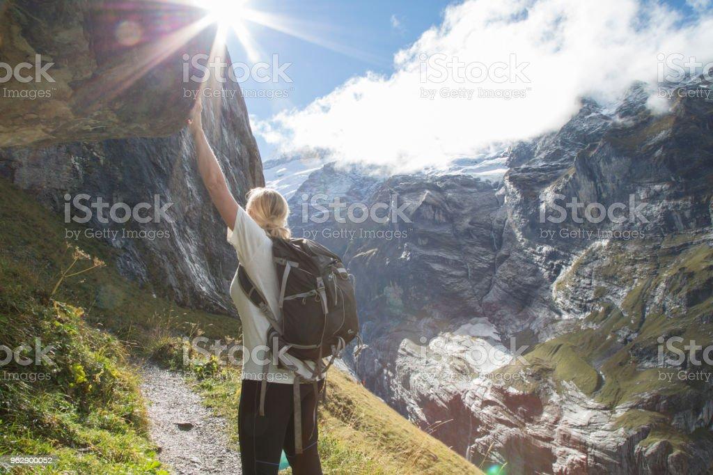 Frau Backpacker lehnt sich an Felsen unterwegs – Foto