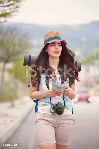 Woman backpacker or photographer with straw hat walking on road