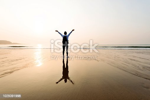 istock Woman backpacker standing on beach with arms raised 1025091998