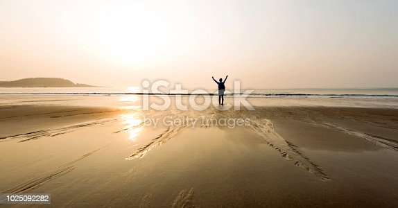 istock Woman backpacker standing on beach with arms raised 1025092282