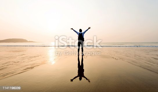 istock Woman backpacker standing on beach with arms raised 1141196039