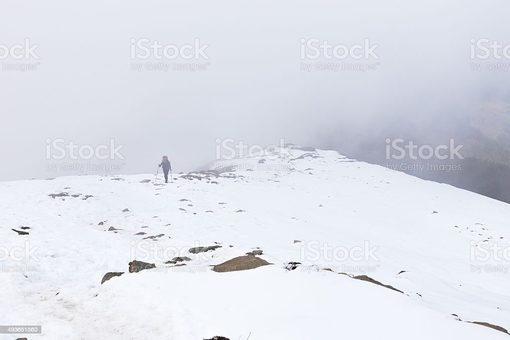 Woman backpacker tourist hiking ascending snow mountain covered fog. stock photo