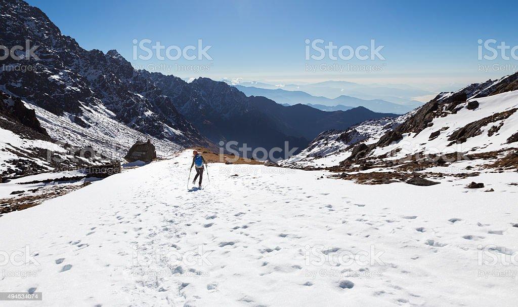 Woman backpacker tourist walking snow mountain back view. stock photo