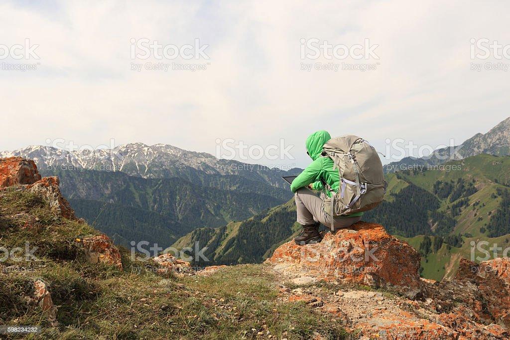 woman backpacker use digital tablet  on mountain peak cliff foto royalty-free