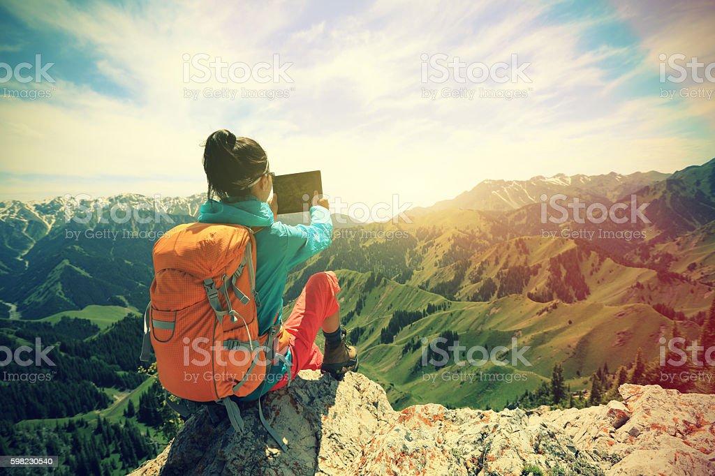 woman backpacker use digital tablet taking photo on mountain peak foto royalty-free