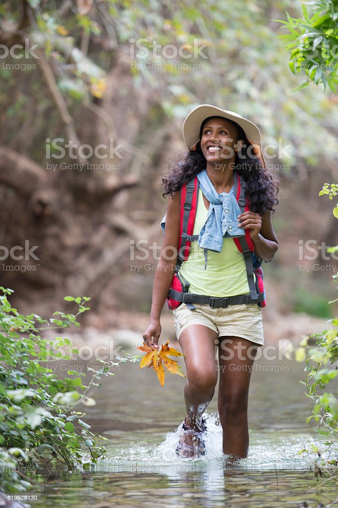 Woman backpacker wading creek in forest. stock photo
