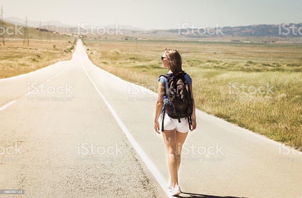 Woman backpacker walking on road royaltyfri bildbanksbilder