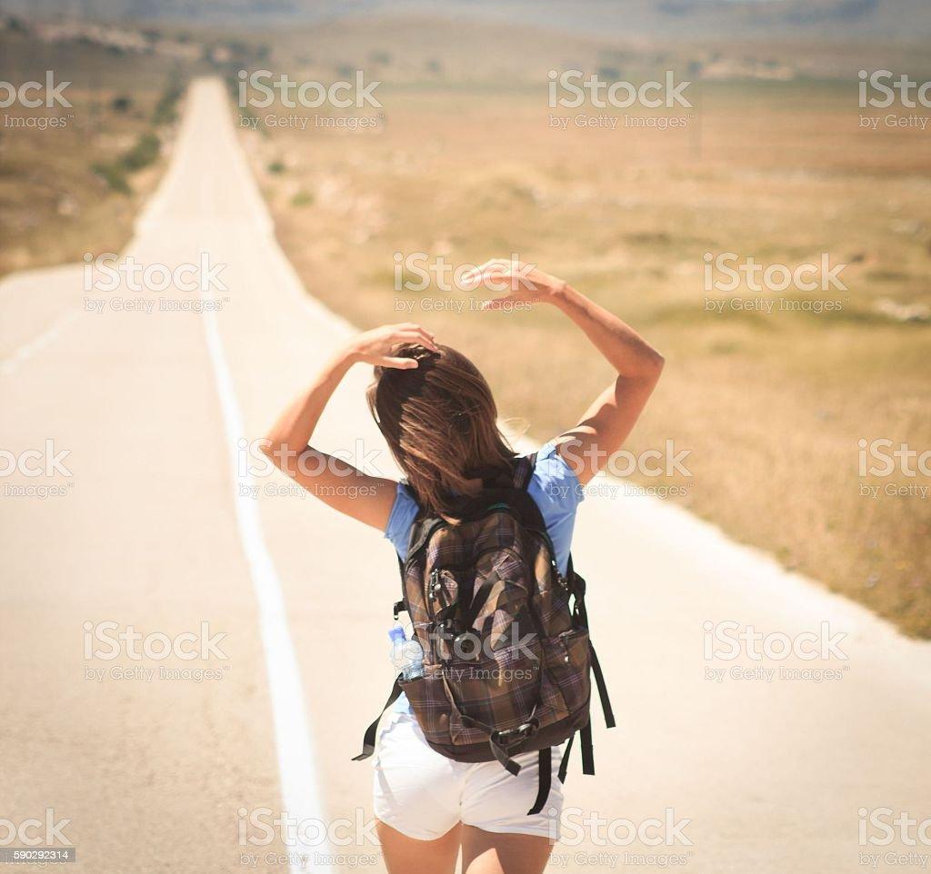 Woman backpacker walking on road Стоковые фото Стоковая фотография