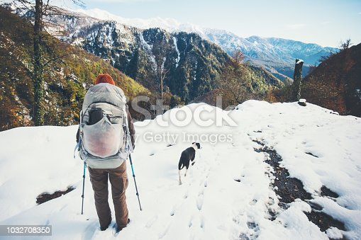 istock Woman backpacker with dog hiking winter mountains Travel Lifestyle concept adventure vacations outdoor 1032708350