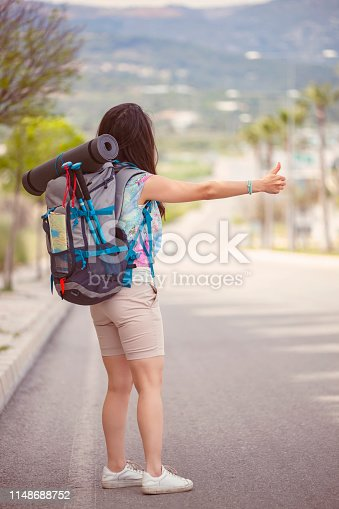 Woman backpacker with straw hat walking on road. hitchhiking woman on road.