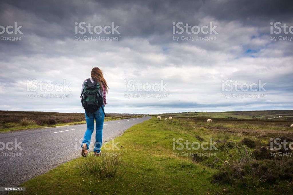 Woman backpacking through England is hitchhiking in North York Moors National Park in England stock photo