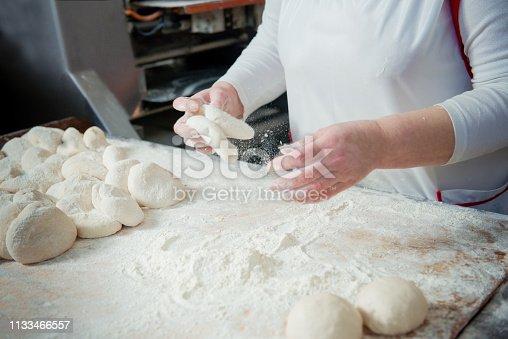 istock Woman baker make buns from dough 1133466557