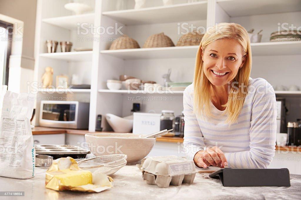 Frau, die sich zu Hause beim Backen versuchen nach Rezept auf tablet – Foto
