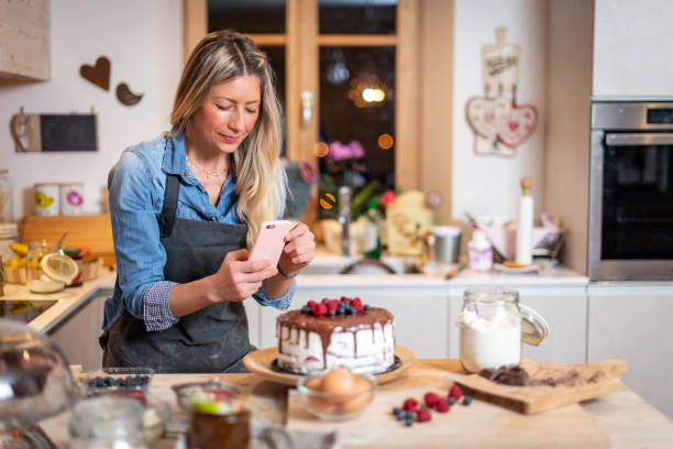 Woman baking at home: Photographing her chocolate sponge cake with berries stock photo
