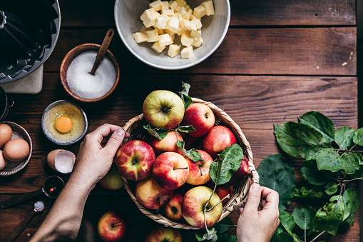Directly above shot of woman with a basket full of freshly picked apples on table with cake baking ingredients. Woman baking cake with freshly picked apples.