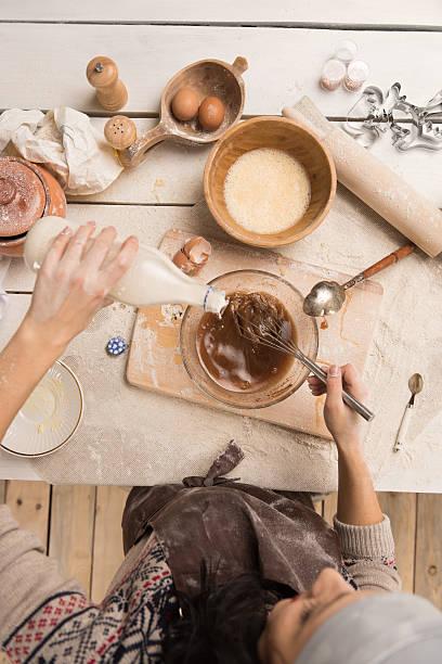 woman baking christmas cookies in her kitchen - hausgemachte zuckerplätzchen stock-fotos und bilder