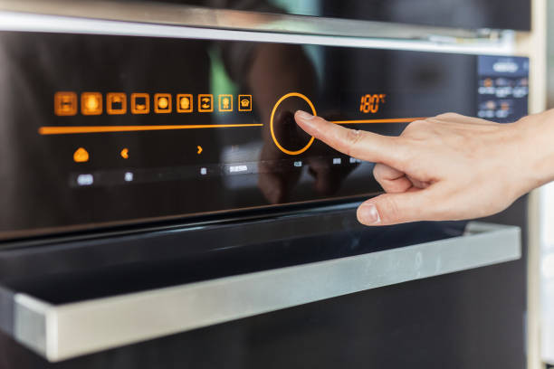 Woman baking cookies in her kitchen Close up of woman's hand setting temperature control on oven. oven stock pictures, royalty-free photos & images