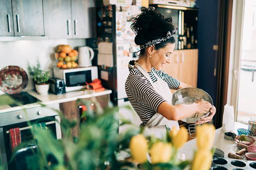 Close-up of a beautiful woman baking muffins