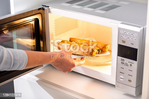 Close-up of a woman baking pastry in microwave oven.
