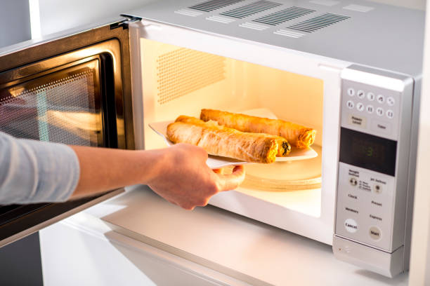 A woman Baking Pastry In Microwave Oven