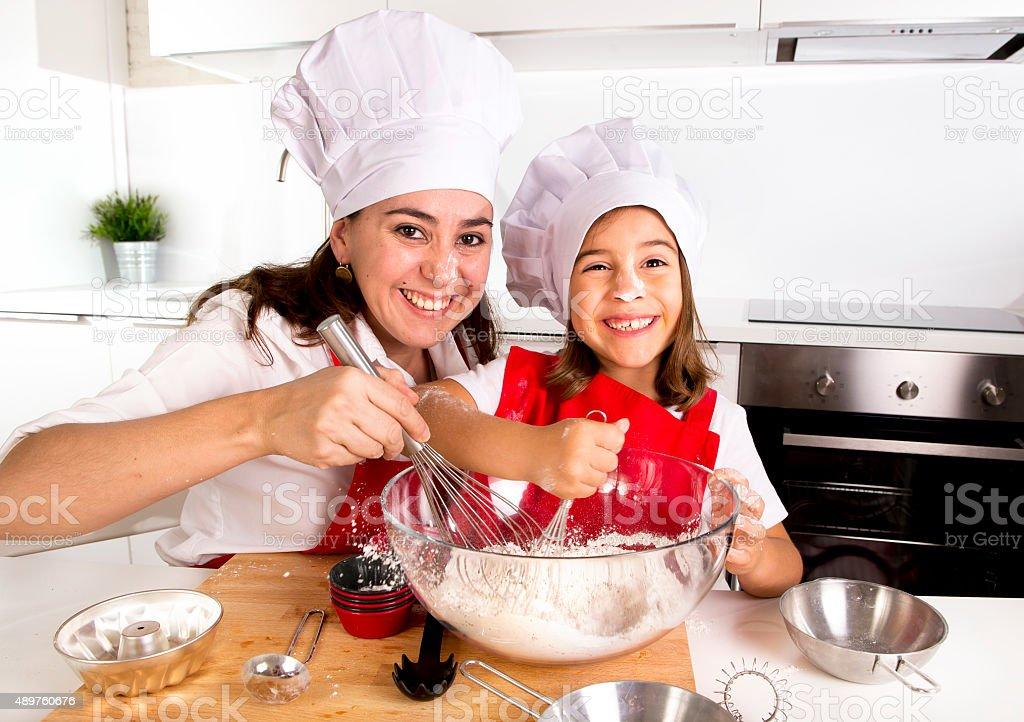 Frau Backen mit kleinen Tochter in Koch-Mütze im kitchen – Foto