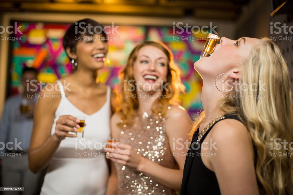 Woman balancing a shot glass on her mouth stock photo