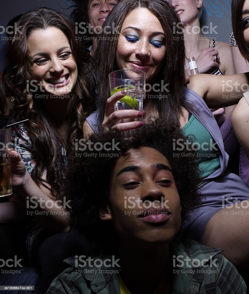 Woman balancing drink on man's head at party royalty free stockfoto