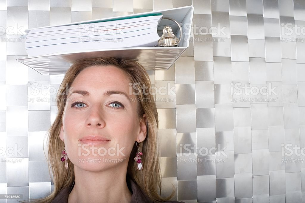 Woman balancing folder on her head royalty-free stock photo