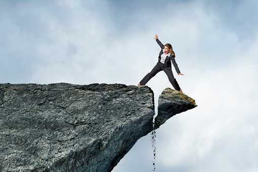 A woman looks down in fear as she straddles the tip of an unstable cliff that is in the process of breaking off.