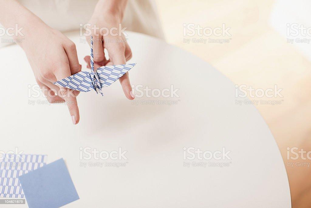 Woman balancing origami bird on fingers royalty-free stock photo