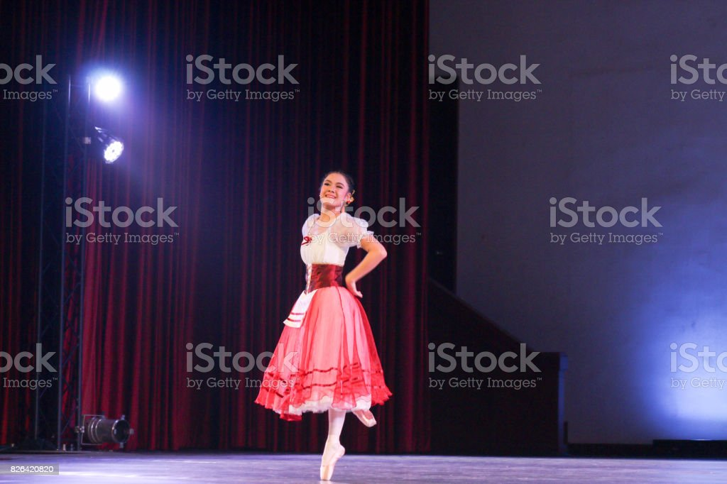 woman ballerina who wear romantic tutu costume on stage stand with...