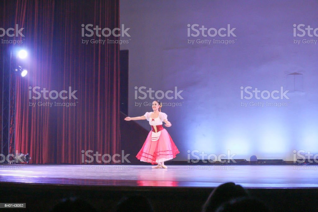 woman ballerina who wear villager costume performs on stage