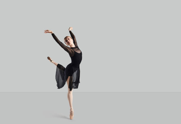 Woman ballet dancer over gray background. stock photo
