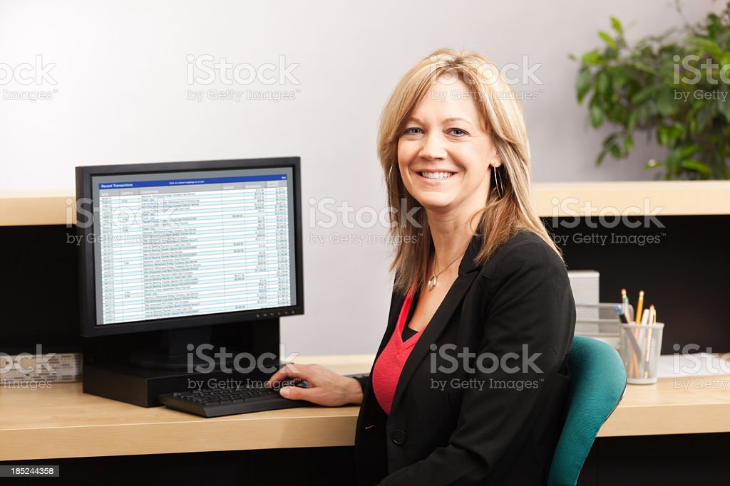 Woman Bank Teller with Computer in Financial Office Building Interior royalty-free stock photo