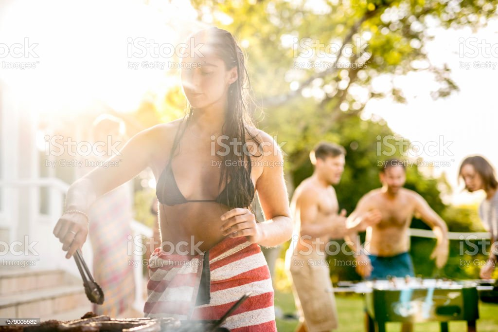 Woman barbecuing in garden party while friends playing. stock photo